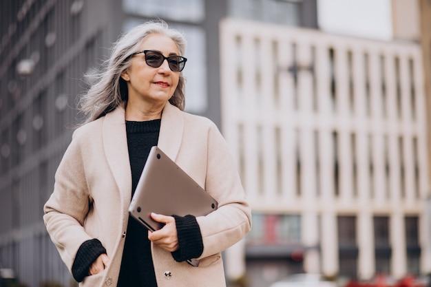 Elderly business woman holding laptop