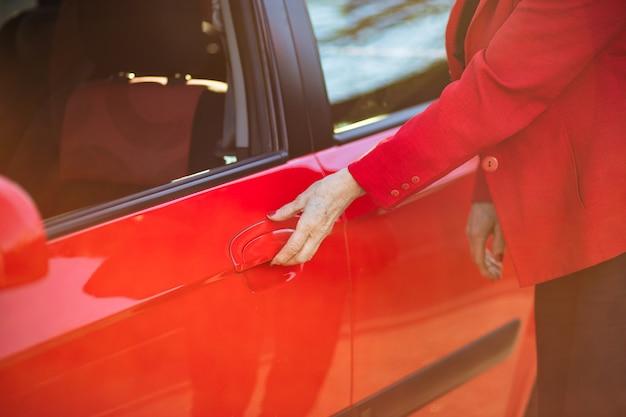An elderly business woman opens the door of her red car