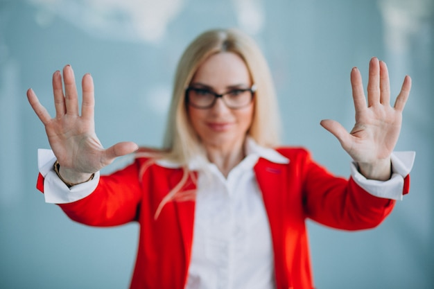 Пожилая деловая женщина показывает руки в красной куртке