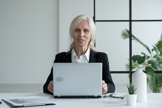 Пожилая деловая женщина работает в офисе с ноутбуком и смотрит в камеру