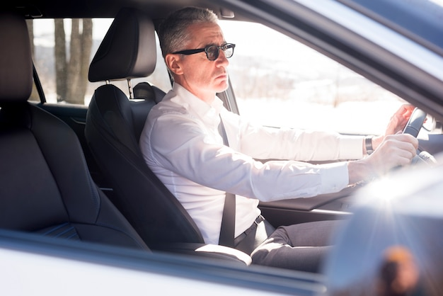 Elderly businessman driving