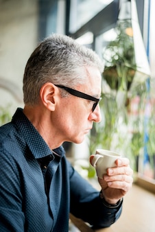 Elderly businessman having up of coffee