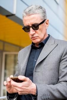 Пожилой бизнесмен смотрит на мобильный телефон