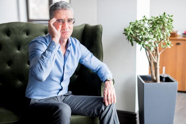 Elderly businessman posing on armchair