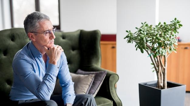 Пожилой бизнесмен позирует на диване