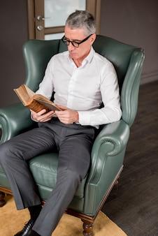 Пожилой бизнесмен читает на кресле