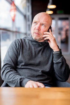 Пожилой бизнесмен разговаривает по телефону