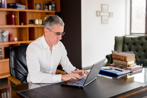 Elderly businessman using his laptop