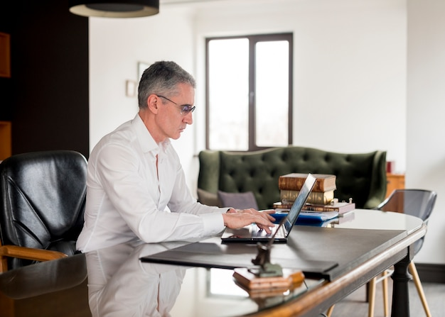 Пожилой бизнесмен, используя свой ноутбук