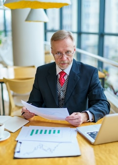 Elderly businessman using laptop and taking notes working while sitting in modern office. selective focus
