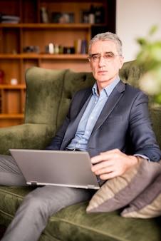 Пожилой бизнесмен используя компьтер-книжку