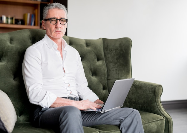 Elderly businessman using laptop