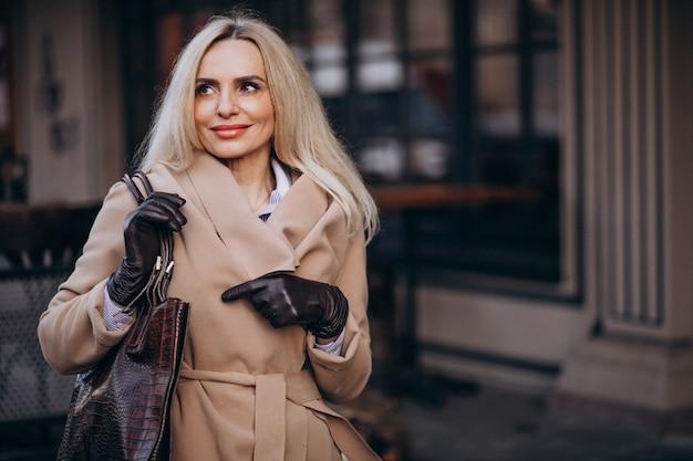 Пожилая деловая женщина в пальто в перчатках на улице