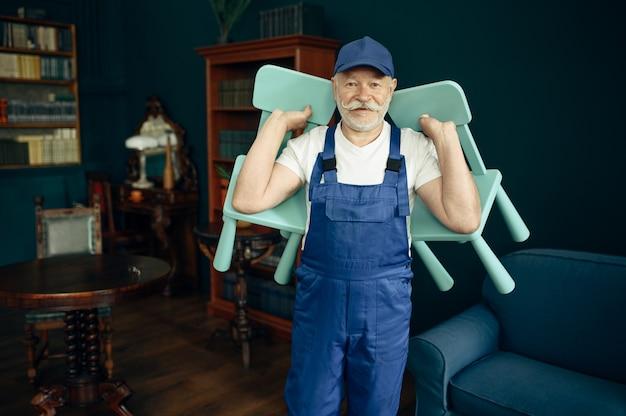 制服を着た年配の荷主が家に子供用の椅子を持っている。成人の配達員、屋内で帽子のポーズで配達、サービスまたはビジネスを配達する
