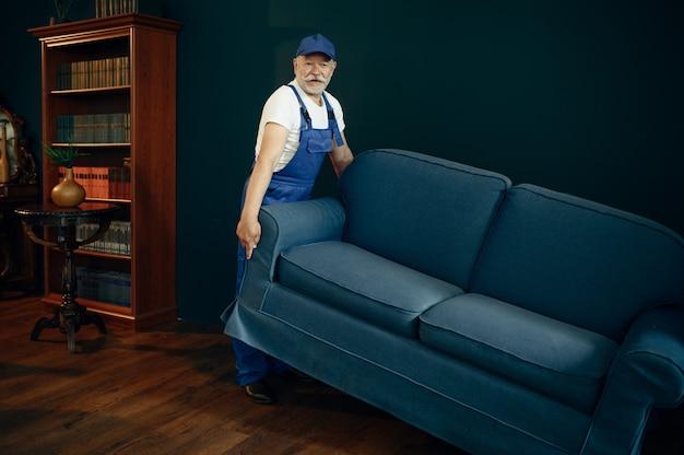 制服を着た年配の貨物男が、ホーム オフィスのソファを移動します。成人の配達員、帽子をかぶった配達は、室内でソファを持ち、サービスやビジネスを配達