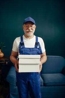 ホームオフィスでの制服ポーズの高齢者の貨物男