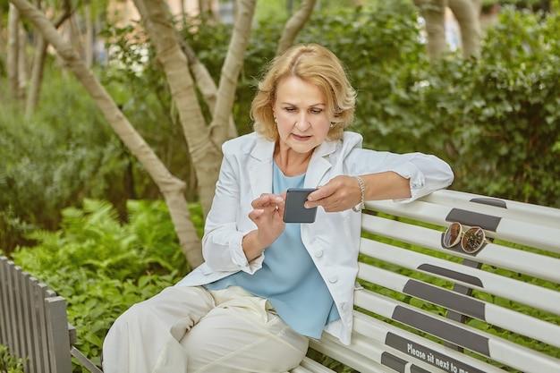 약 60 세 노인 백인 매력적인 여자는 낮에 손에 스마트 폰으로 공공 공원 벤치에 앉아있다.