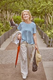 Elderly caucasian attractive woman about 62 years old is walking in public park.