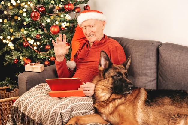 Пожилой кавказский мужчина в шляпе санты с планшетом сидит на диване возле елки с подарочной коробкой и немецкой овчаркой болтает с родственниками в интернете. самоизоляция, праздничное настроение.