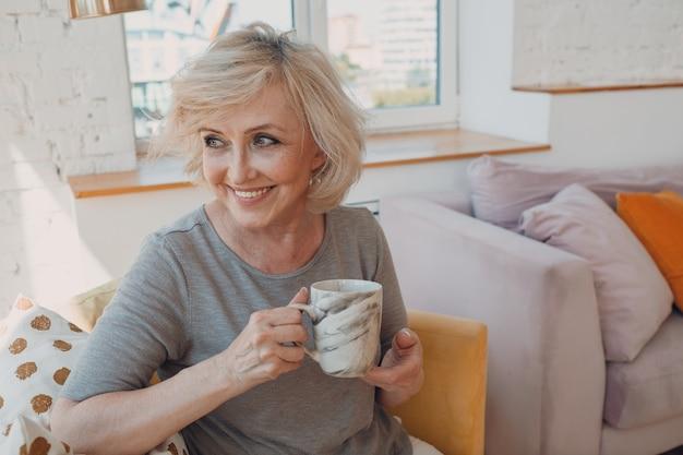 自宅でアフタヌーンティーを楽しんでいる高齢の白人の老婆。