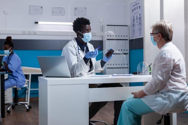 薬の瓶を取得している高齢の白人患者