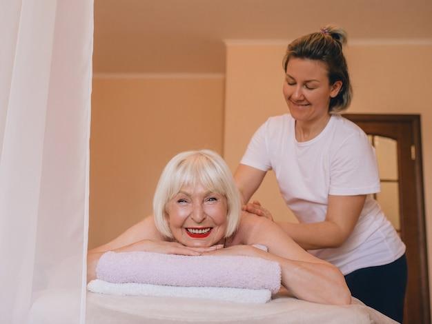 タイ式マッサージで彼女の髪に白髪とピンクの胡蝶蘭を持つ年配の白人のスタイリッシュな女性