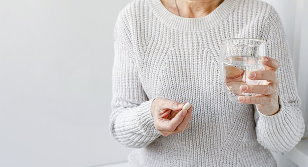 Elderly caucasian woman holding pill and a glass of water. copy space