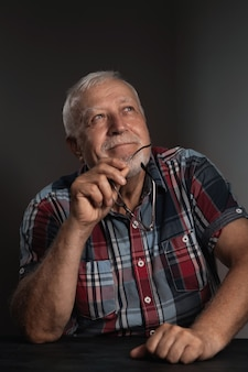 Elderly charismatic man in a checkered shirt, holds glasses in his hands and looks to the side, close-up portrait on a gray background