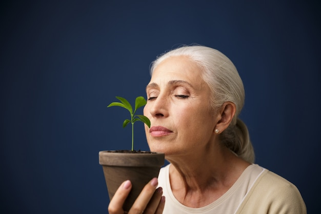 Elderly charming woman sniffs young plant with eyes closed