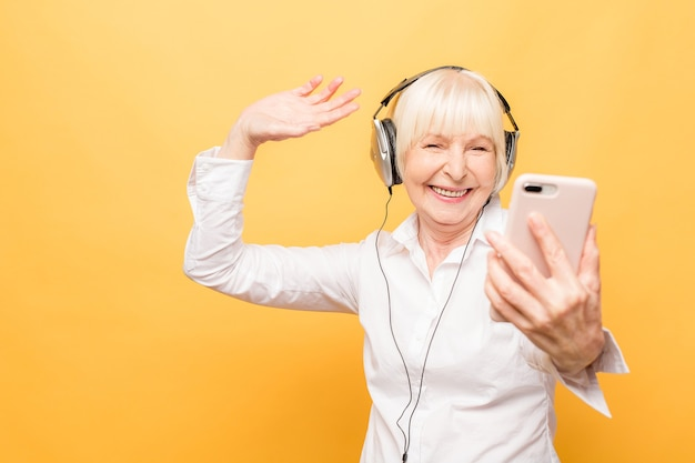 Elderly cheerful woman with headphones listening to music on a phone and dancing isolated on yellow background.