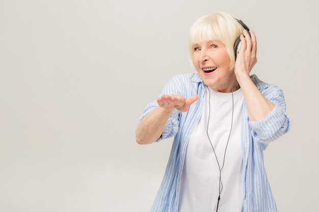 Elderly cheerful woman with headphones listening to music on a phone isolated on white background.