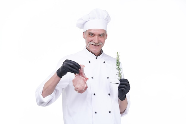 Elderly chef holds vegetation and meat