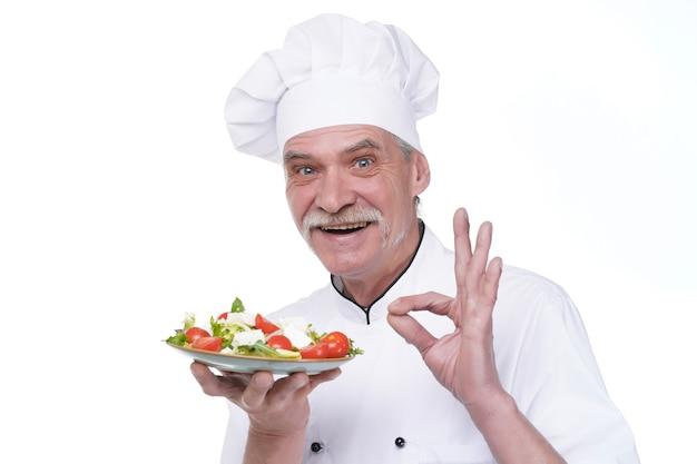 白い制服を着た年配のシェフは、野菜サラダ滞在孤立した白い壁を保持します