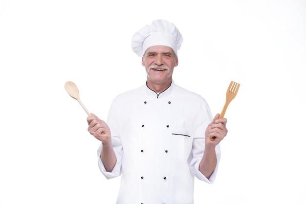 Пожилой старший мужчина в форме повара улыбается, держа ложку и вилку, изолированные на белой стене