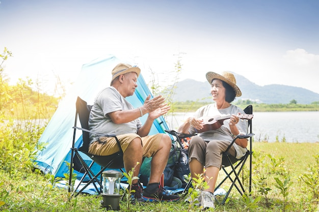 Elderly couple camping in a forest by the river. both sit on a chair and play music. happy life in retirement. senior community concepts