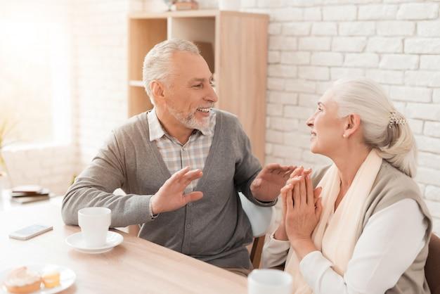 Пожилая пара общается дома.