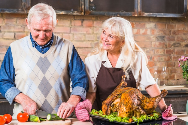 Elderly couple cooking turkey with vegetables