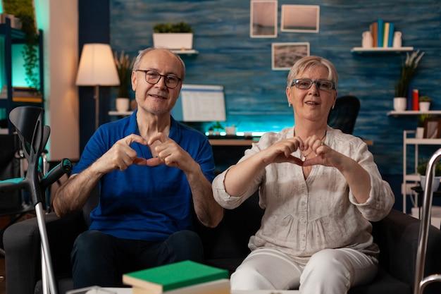 手でハートの形を作る老夫婦