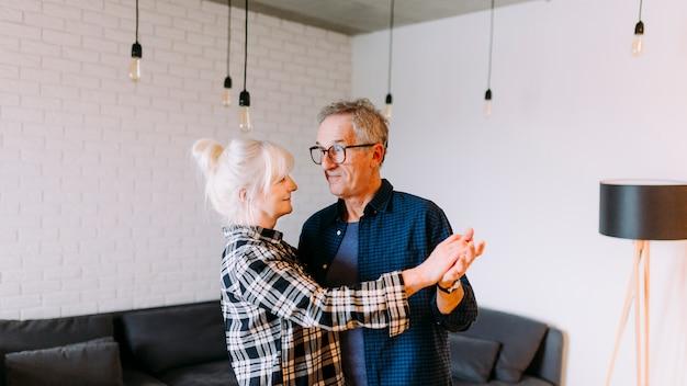 退職の家で踊っている高齢者のカップル