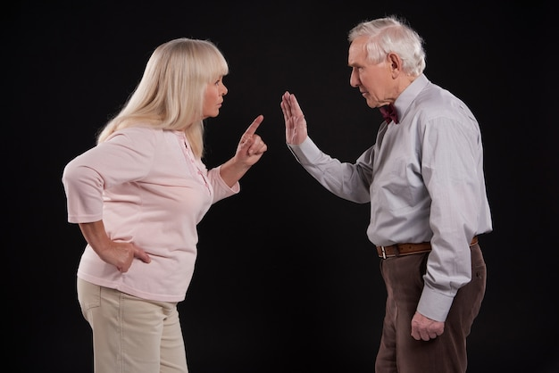 Elderly couple discussing isolated on black background.