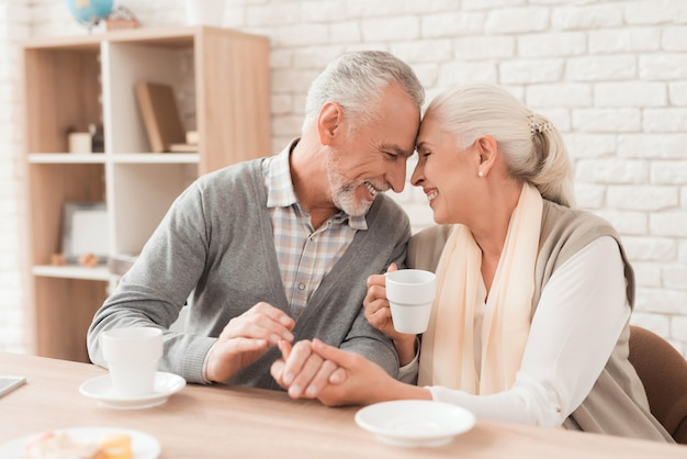 Elderly couple drinking coffee, holding hands together.