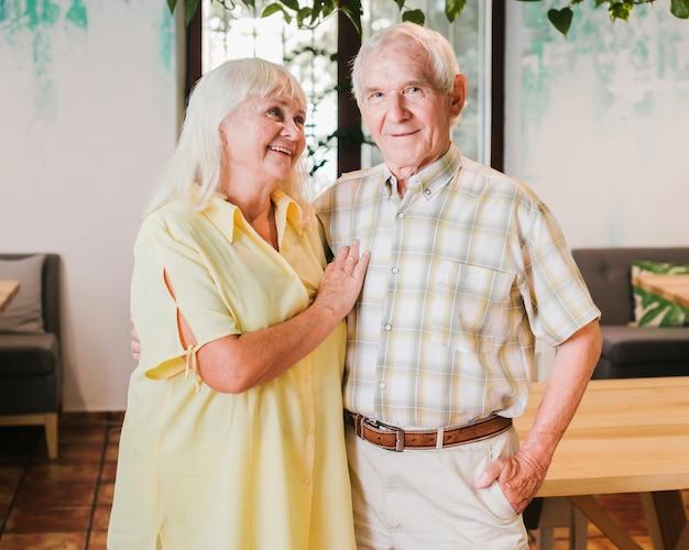 Пожилая пара обнимается, стоя у себя дома
