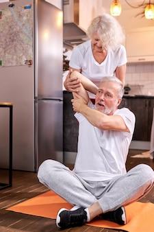 自宅で運動している老夫婦、女性は床に座って、夫がストレッチするのを手伝います。幸福、健康的なライフスタイルの概念