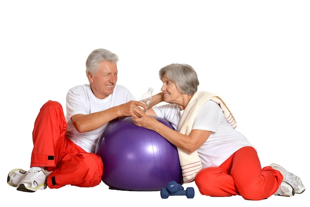 Elderly couple exercising,sitting on a floor of a gym isolated on white