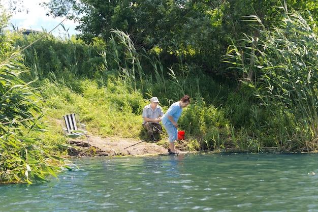 조용한 민물 호수에 노인 부부 낚시