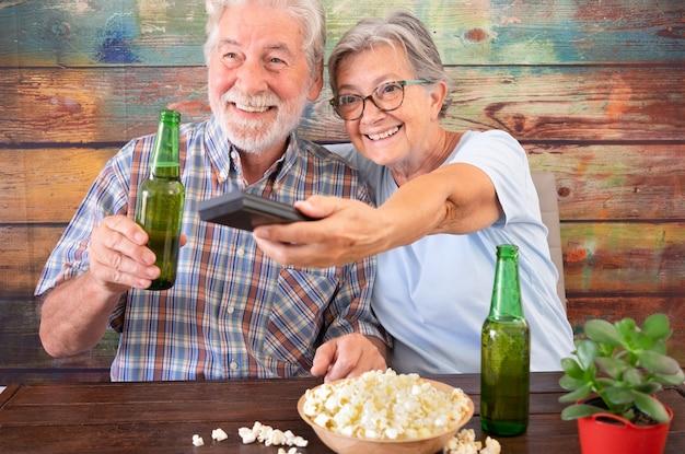 노인 부부는 tv에서 축구 경기를 보는 재미. 테이블에 맥주와 팝콘 병