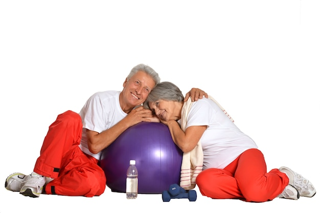 Elderly couple having a rest on a floor of a gym isolated on white