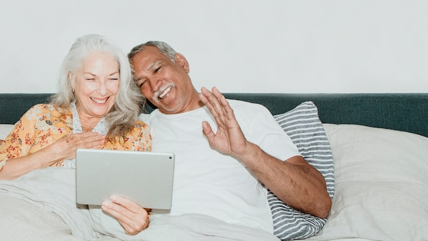 Elderly couple having a video call in bed