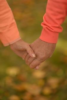 秋の公園で手をつないでいる老夫婦