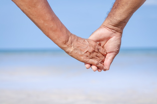 Elderly couple holding hands to travel to the sea take care
